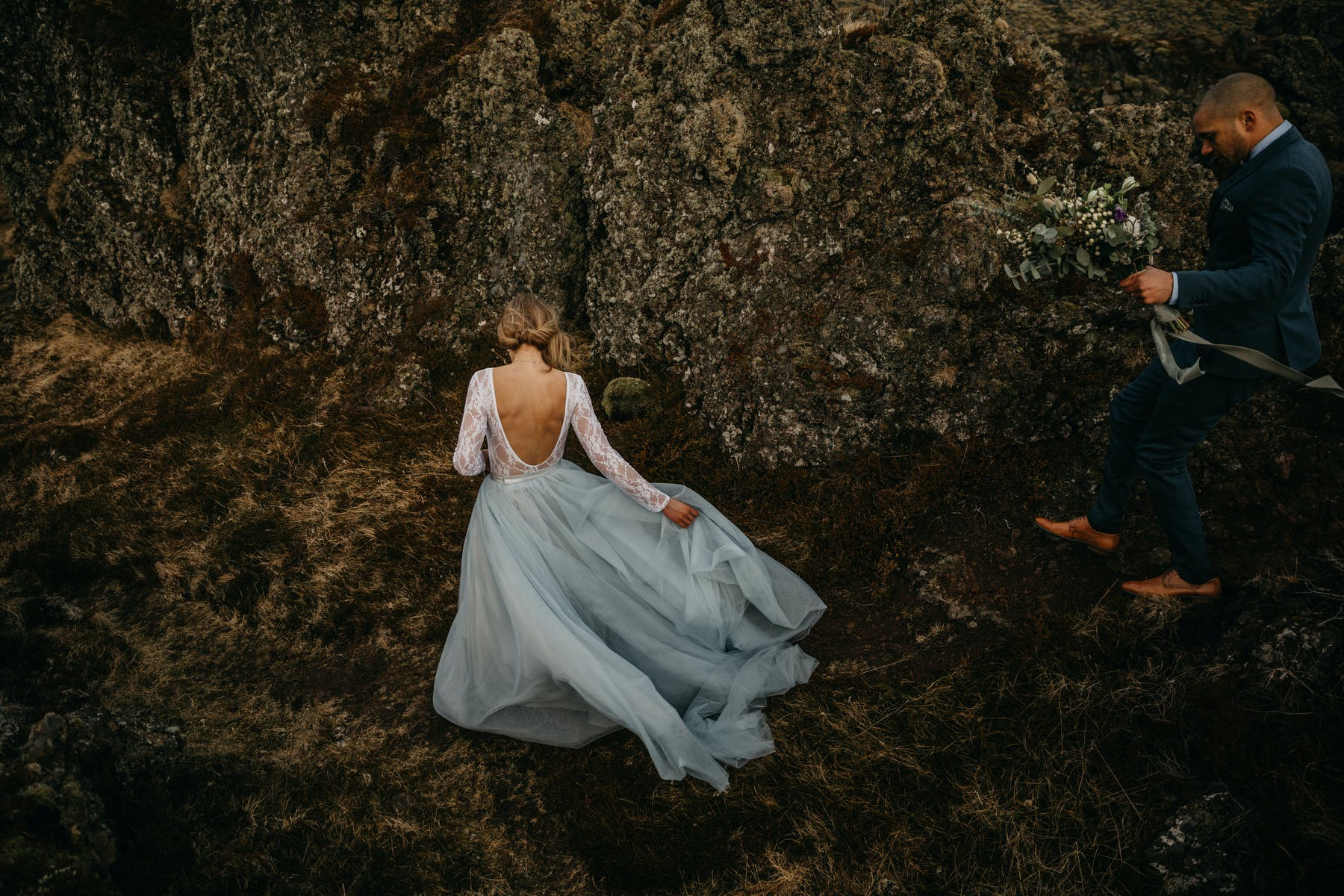 Bride and groom walk on rocks in Iceland