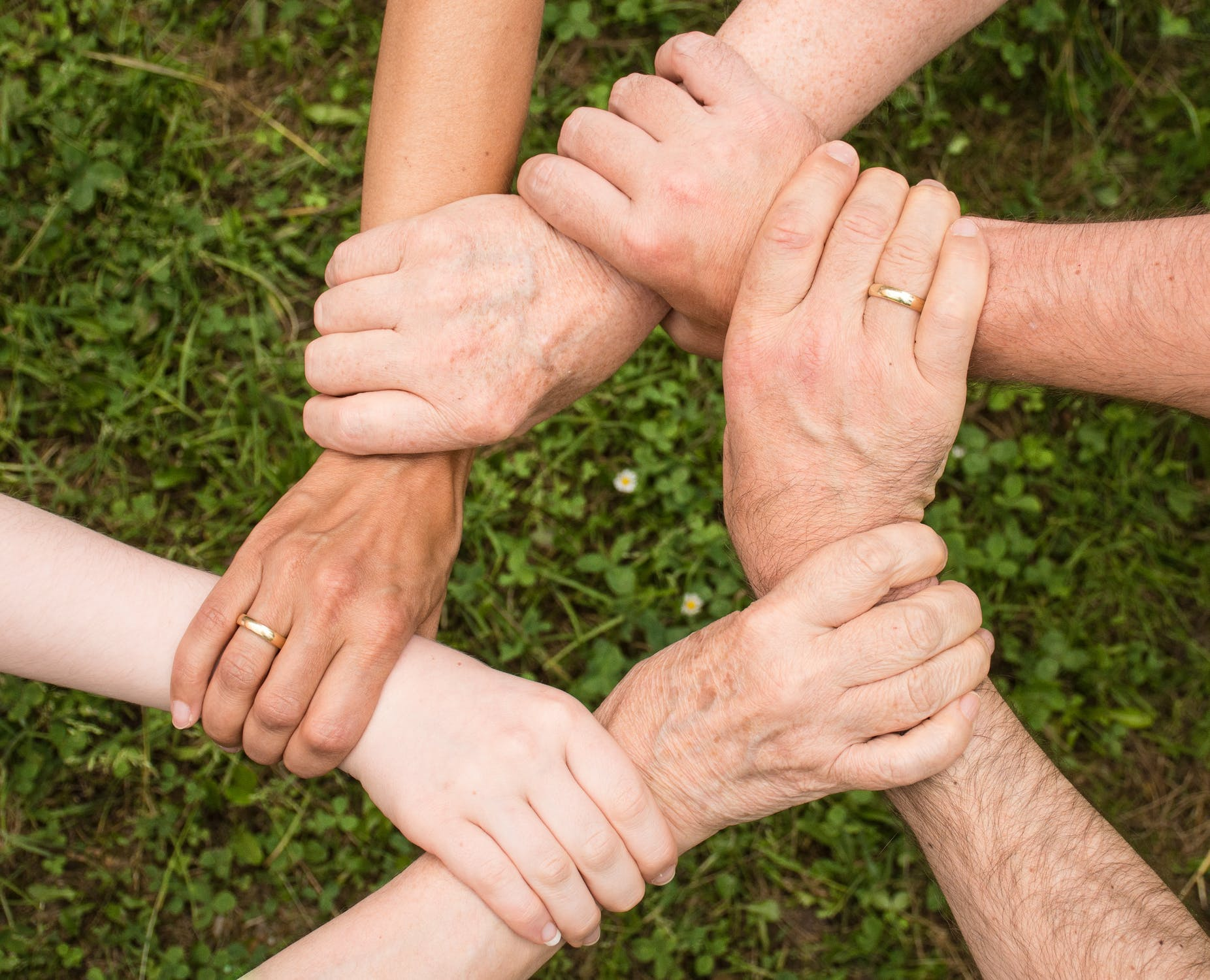 Six people holding their hands forming a circle