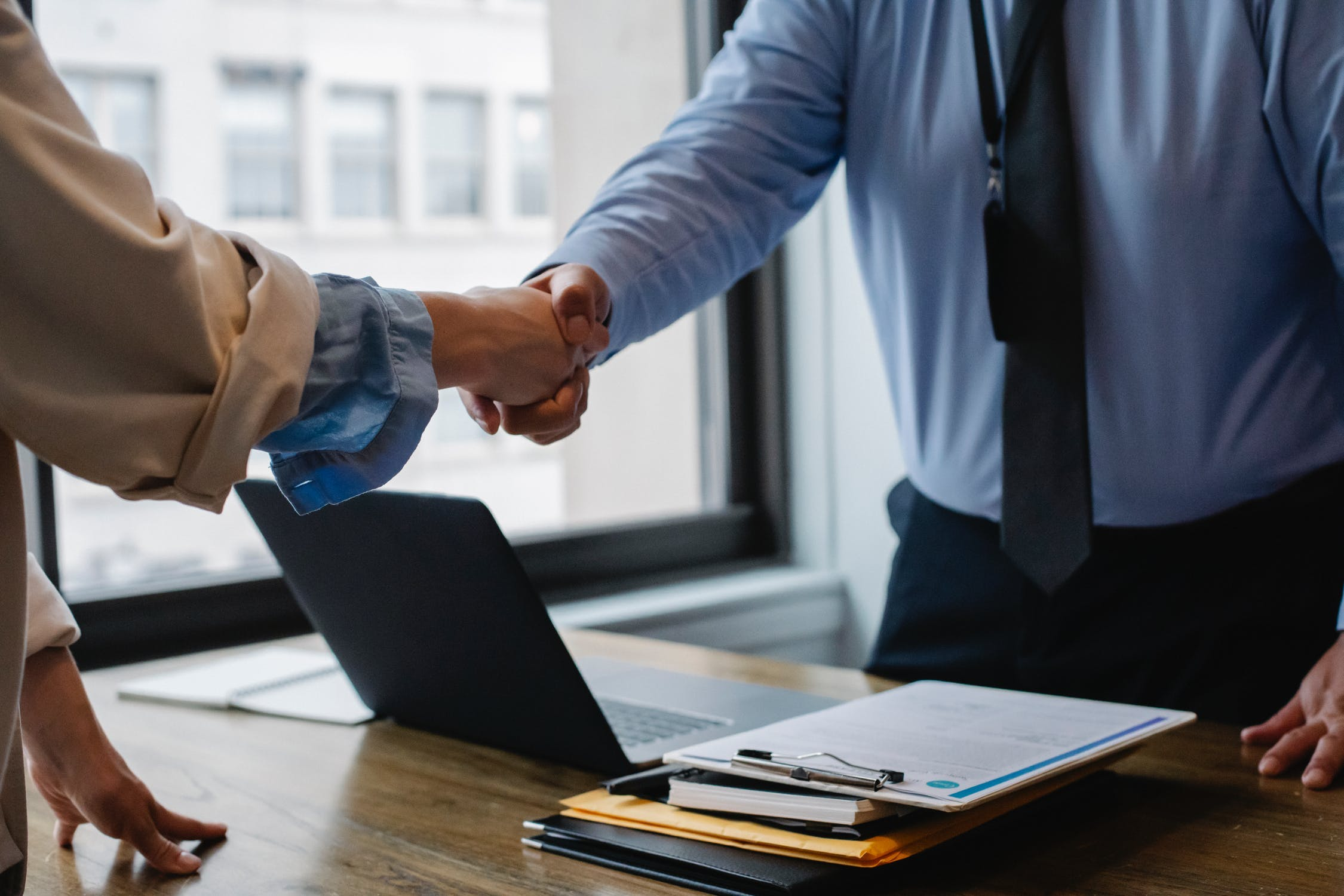 Two people shaking hands in a company office