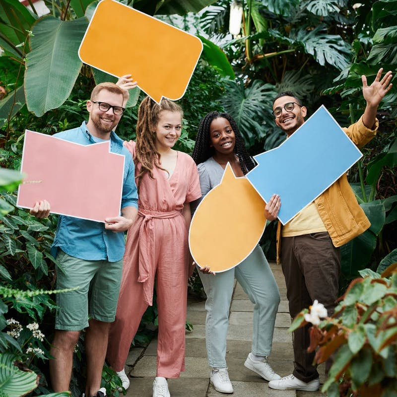 Four people holding cardboard thought bubbles
