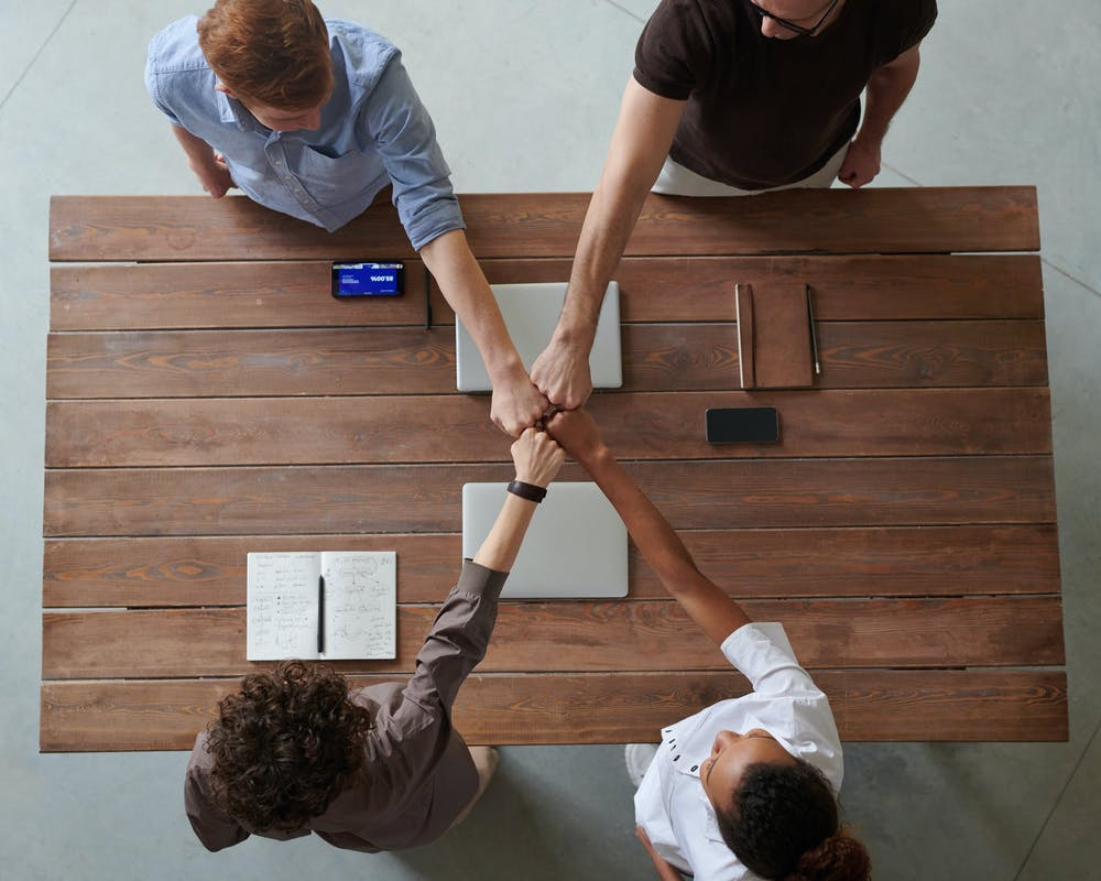 Four people fist bumping across a table