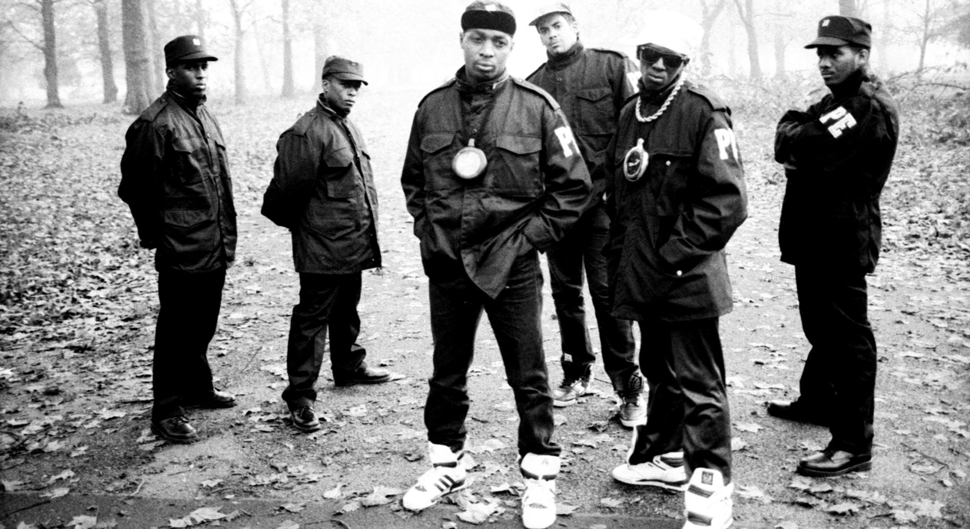A member of the security organization S1W or 'Security Of The First World', S1W, Professor Griff, Chuck D, Terminator X, Flavor Flav, and another member of S1W of the rap group 'Public Enemy' pose for a portrait on November 2, 1987 in Hyde Park in London, England.