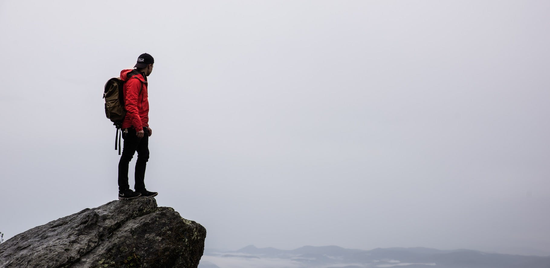 Tramper with a backpack on standing on the edge of a rock over looking a valley