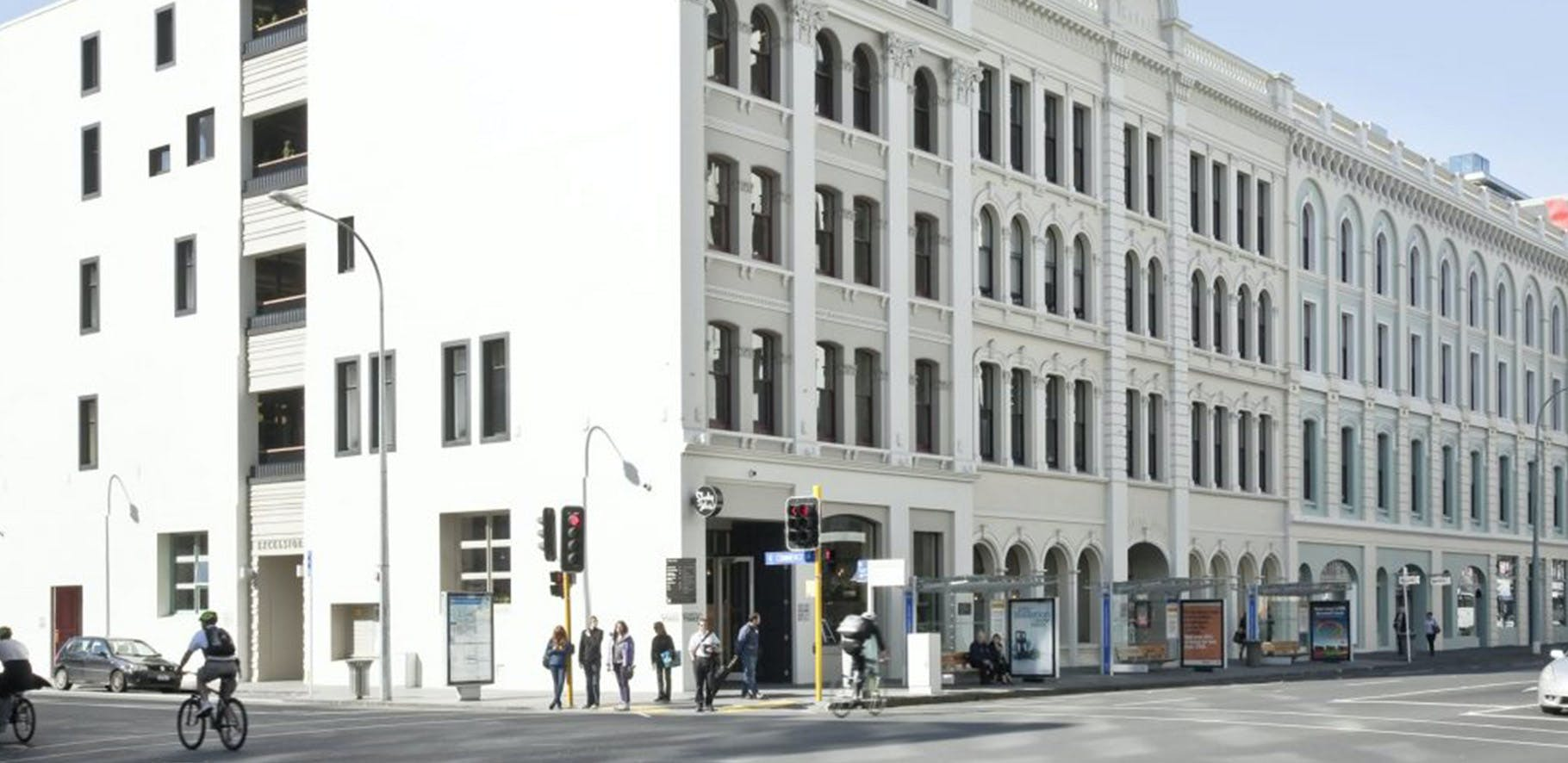 people standing on a street corner waiting for the lights with a big building behind them