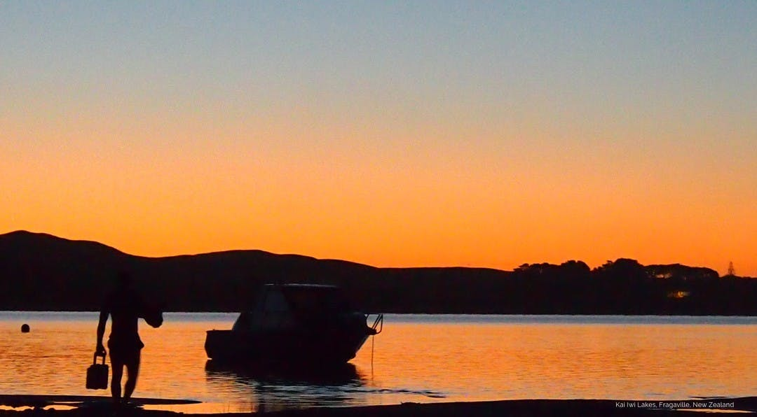 sunset lanscape image with a black silhouette of a man walking to his boat which is moored on the beach.