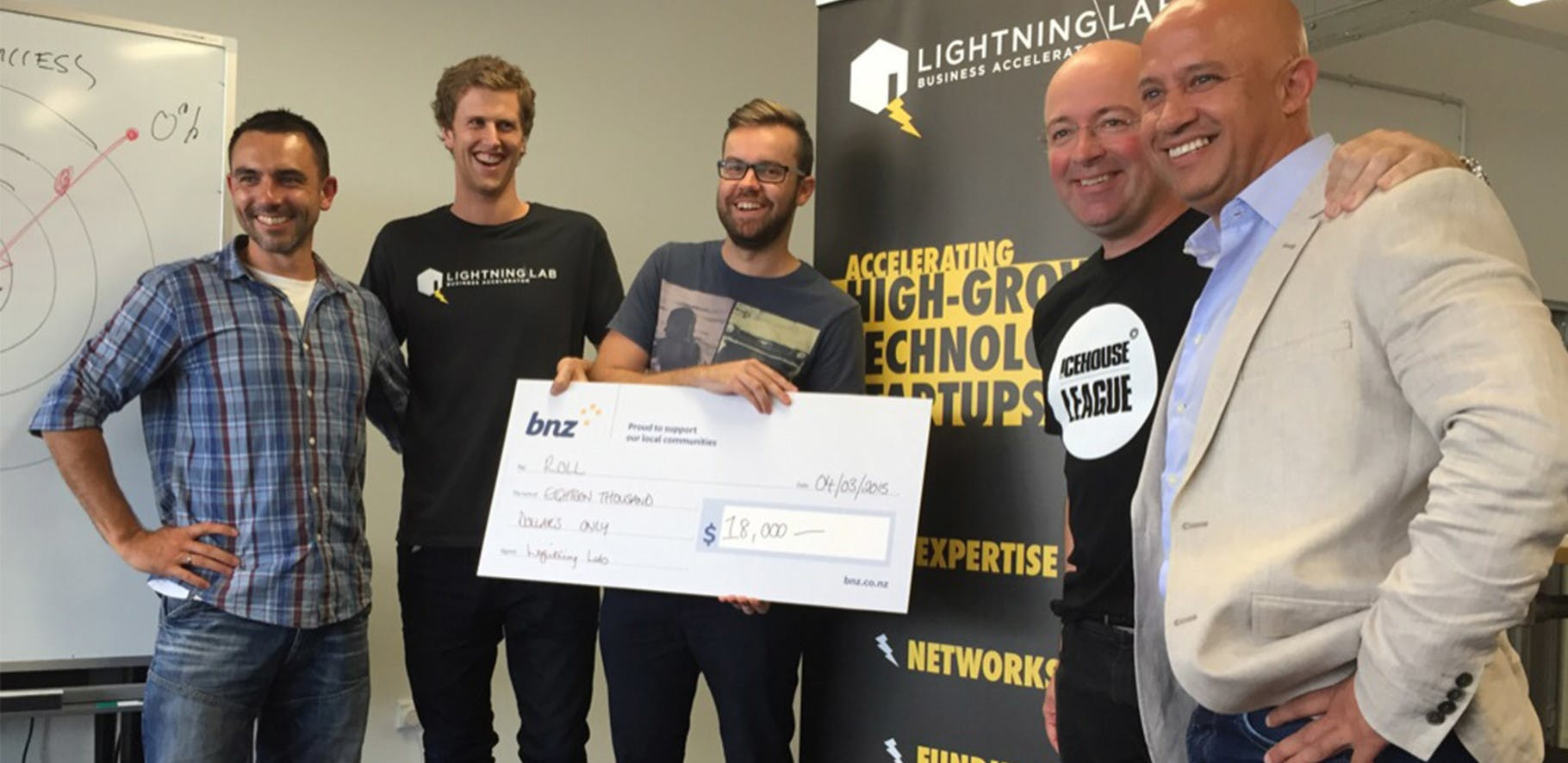 The team at Roll are being presented with a cheque from Lightning Lab for being chosen as one of the 9 most promising tech startups in New Zealand