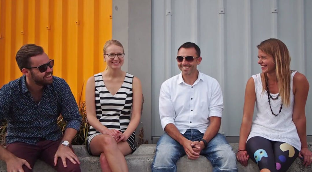 group of 4 people sitting down in an industril area talking and smiling.