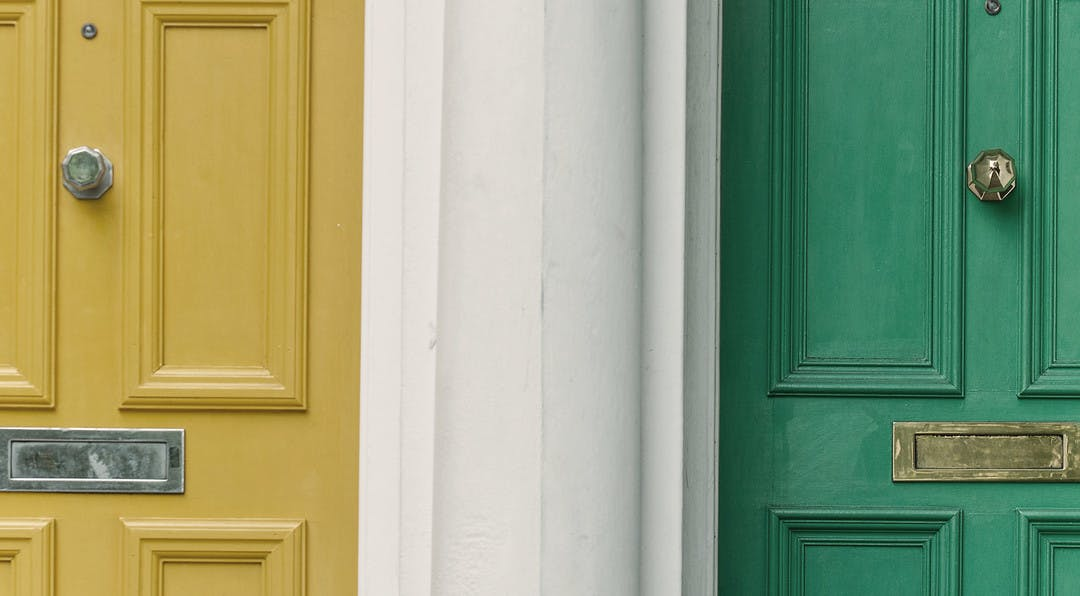 two doors are seperated by a white wall, there is a yellow door on the left and a green door on the right.