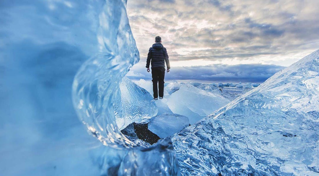 close up image looking through glacier ice, with a man standing in the background looking out over the vast glacier