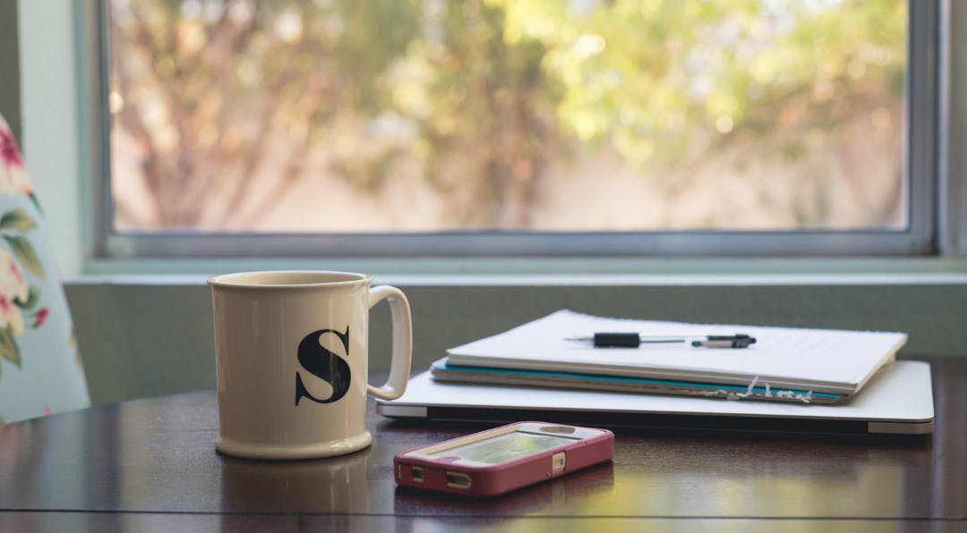 coffee cup and phone with project management papers on table