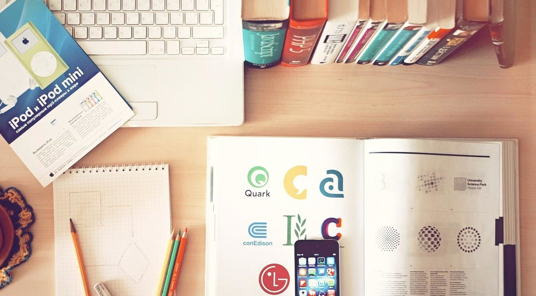 looking down onto an office desk which shows a lap, notepad, pencils, phone and an open book