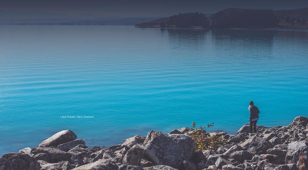 Women walking down some rocks to the edge of a beautiful blue lake