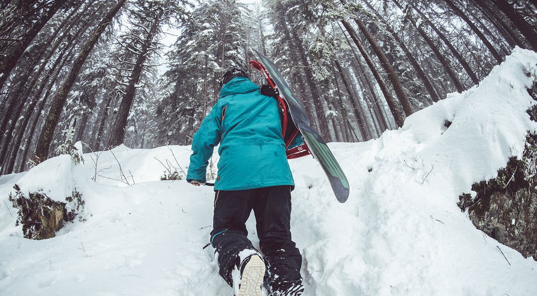 snowboarder carrying his board on his back tramping through the snow amongst the trees