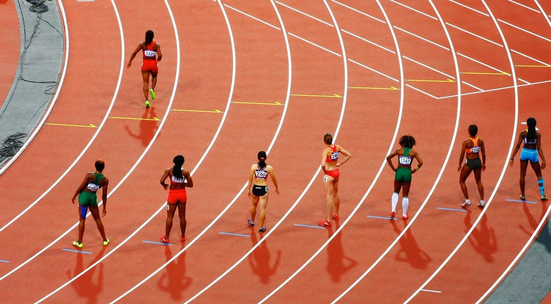 Track and field athletes lining up to start a race while one runner is already off running ahead of everyone else.