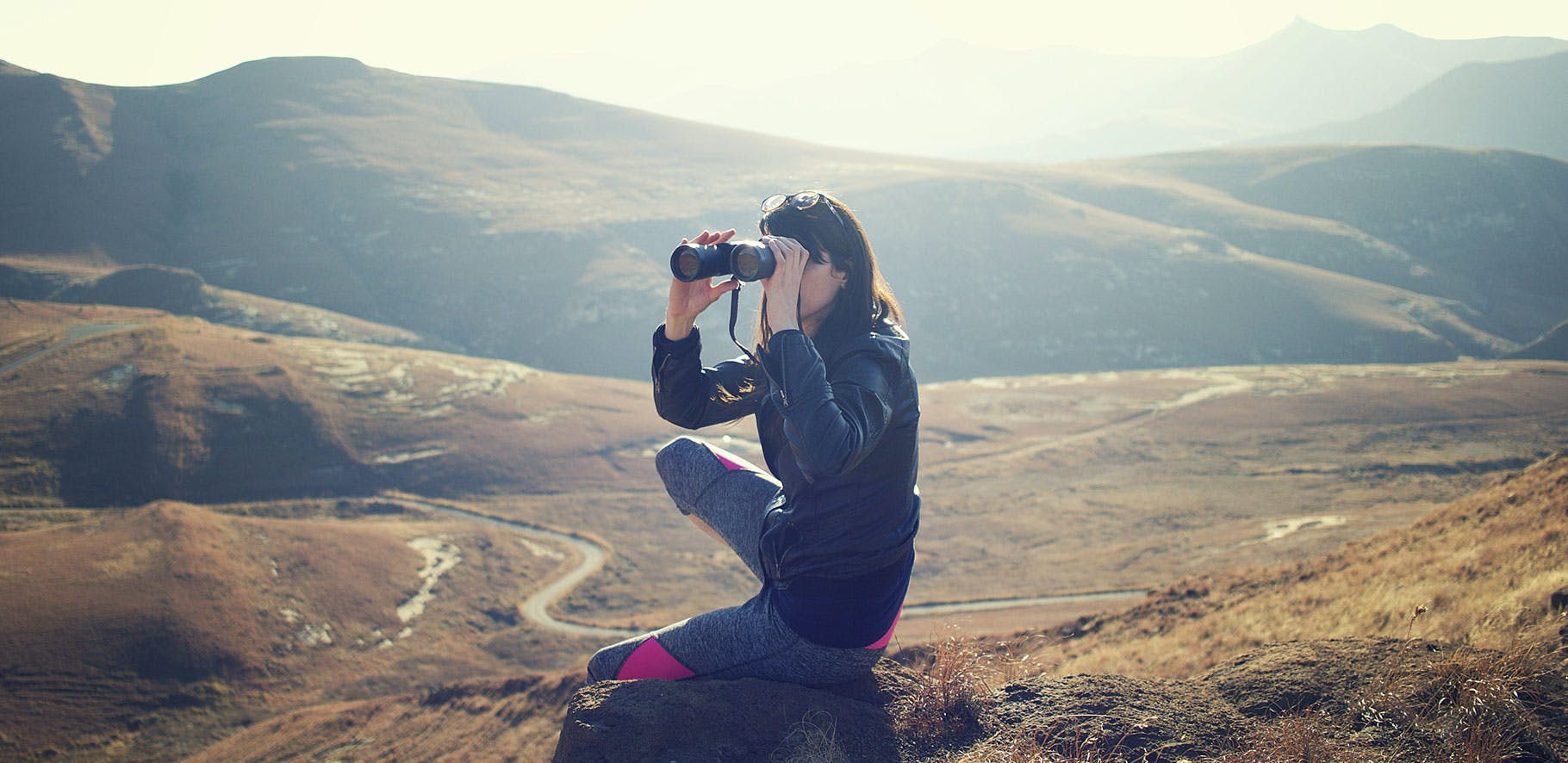 woman using binoculars sitting on a hill with the valley behind her in the background