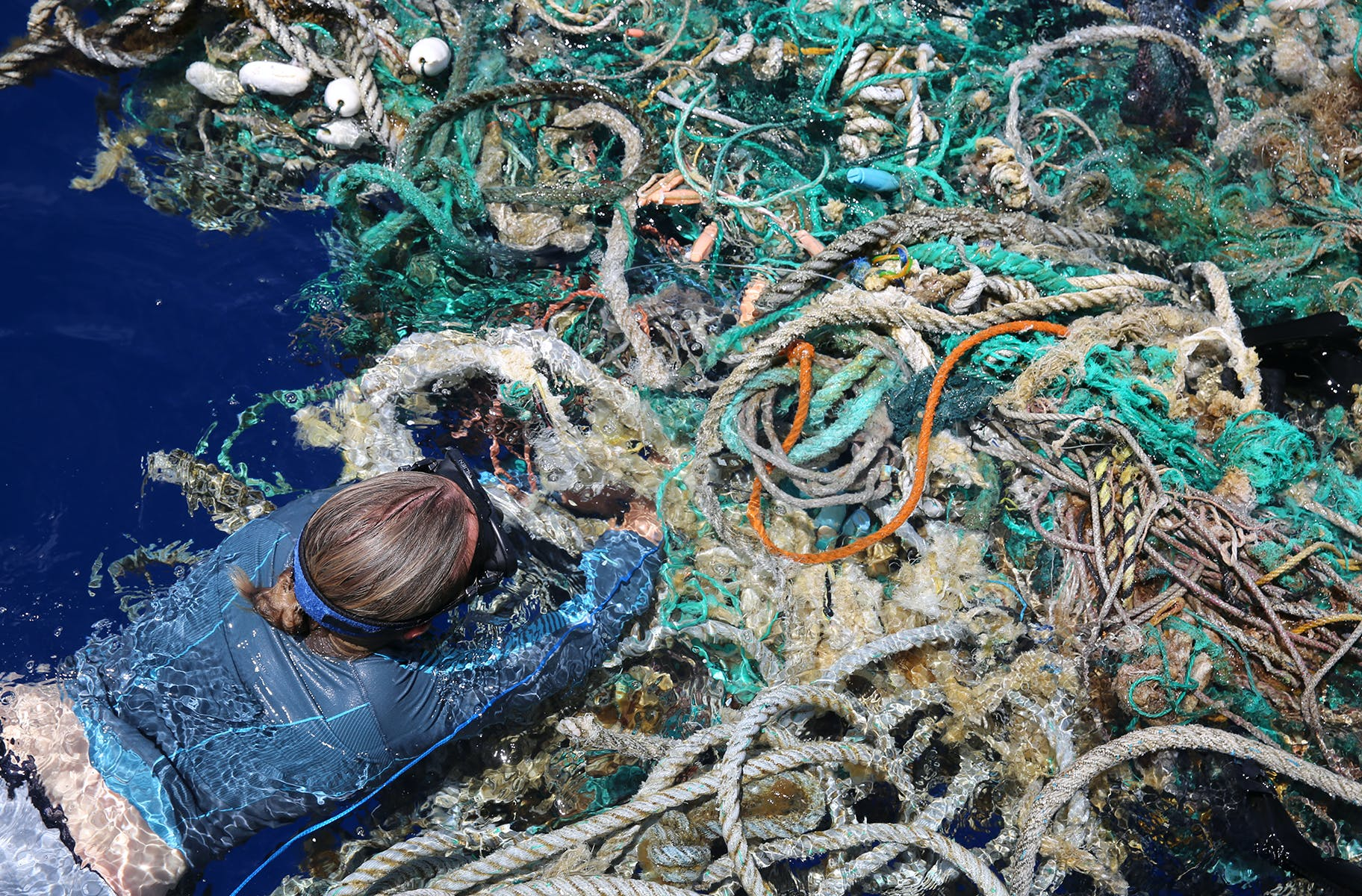 Member of the eXXpedition crew taking a plastic sample in a garbage patch on the ocean.