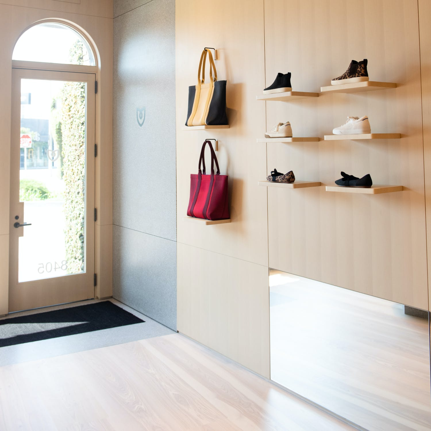 The inside of the Melrose store with bags and shoes displayed.