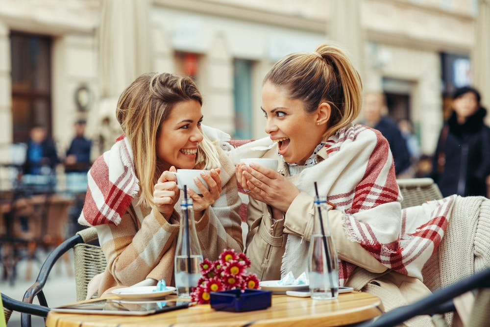 Two women at an outdoor table holding up cups of coffee during brunch