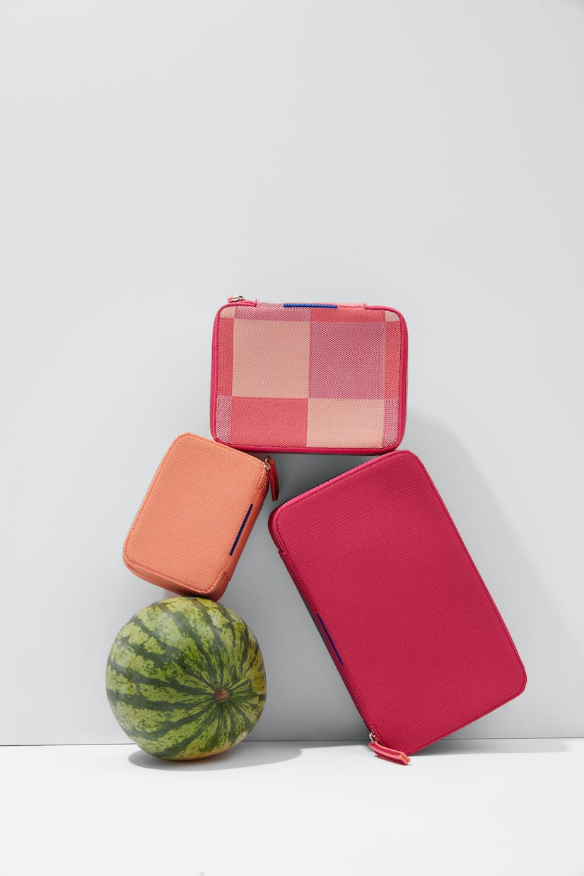 The Mini Catchall in Light Melon, The Mid Catchall in Peach Madras and The Large Catchall in Bright Fuchsia shown balanced with a watermelon.