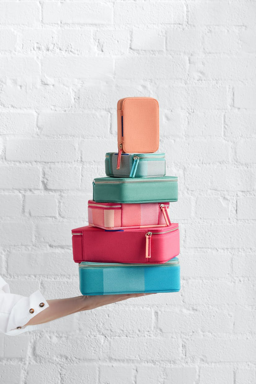The Mini Catchall in Light Melon, The Mini Catchall in Juniper Madras, The Mid Catchall in Juniper Green, The Mid Catchall in Peach Madras, The Large Catchall in Bright Fuchsia and The Large Catchall in Caribbean Madras shown stacked.