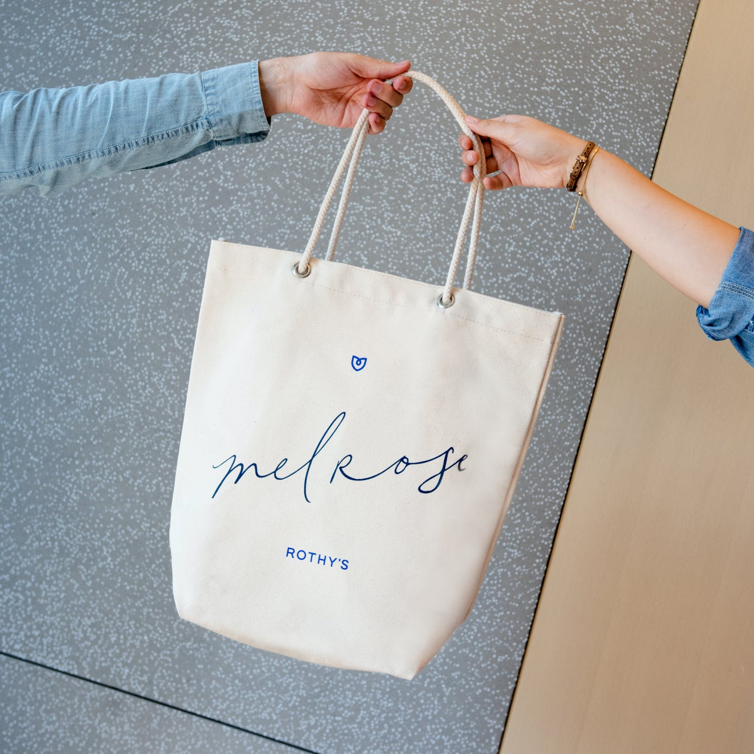 Melrose exclusive tote held by two Rothy's employees.