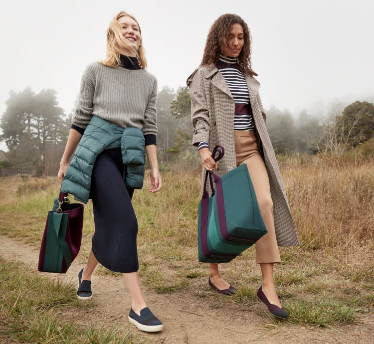 Two models holding The Bucket Bag in Dark Plum and The Essential Tote in Deep Spruce wearing The Sneaker in Night Stripe and The Flat in Blackberry Captoe.