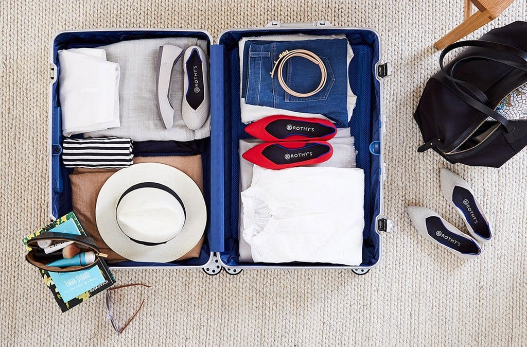 An open luggage with folded clothes, a hat, and two pairs of Rothy's flats.