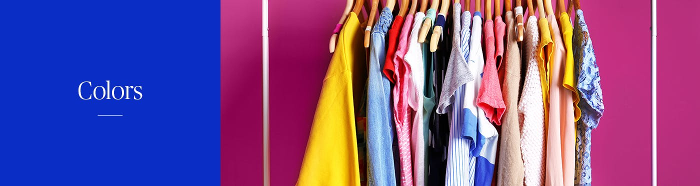A variety of colorful shirts hanging off a rack