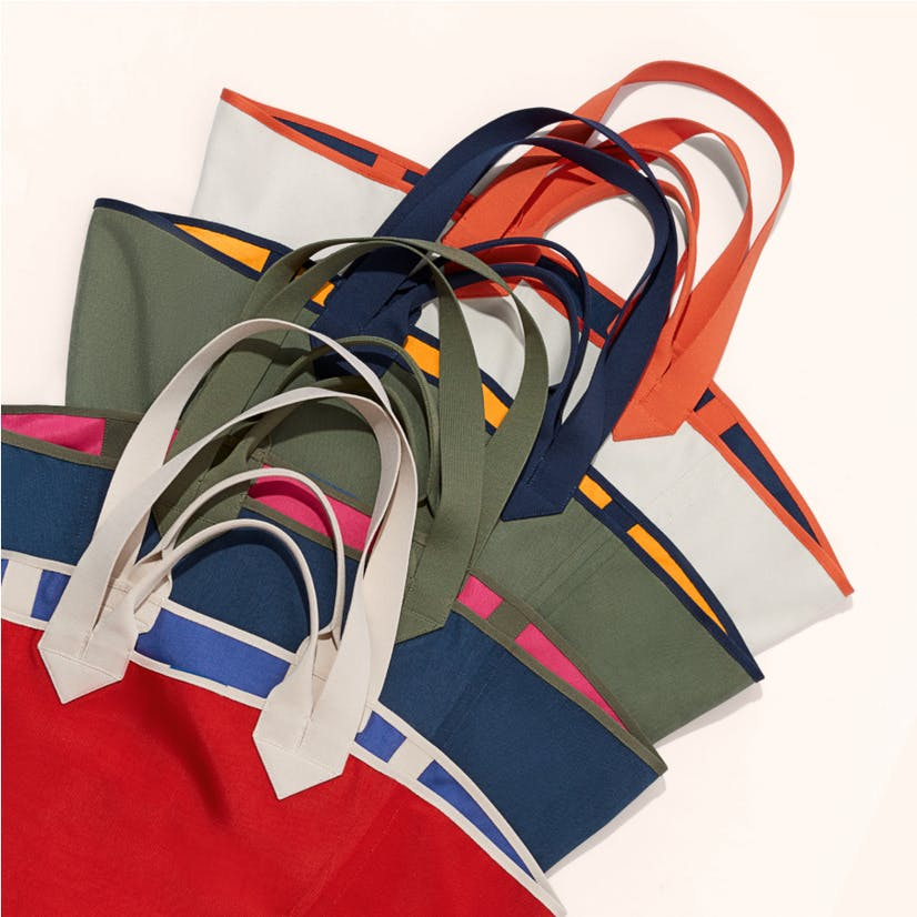 The Reversible Tote in Red & Cobalt, The Reversible Tote in Navy & Pink, The Reversible Tote in Olive & Yellow, The Reversible Tote in White & Navy shown in a laydown.