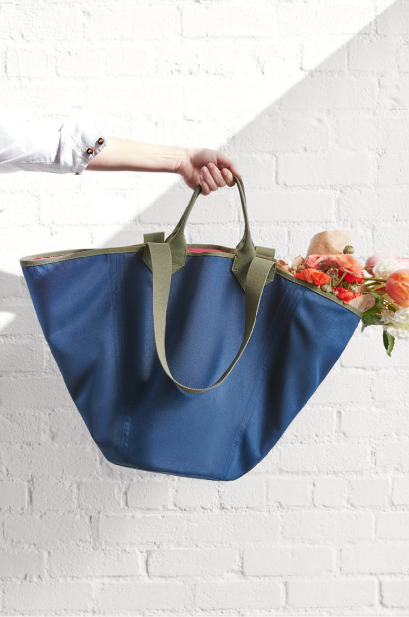 The Reversible Tote in Navy & Pink held by a model with flowers inside.