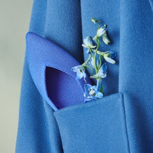 The Point in Cornflower shown in the pocket of a blue coat.