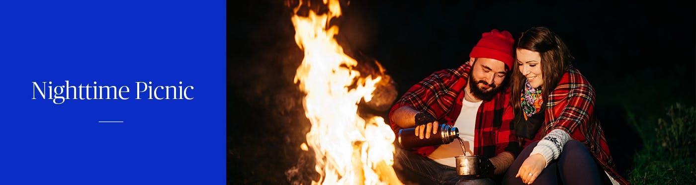 Man and woman sitting near a campfire at night
