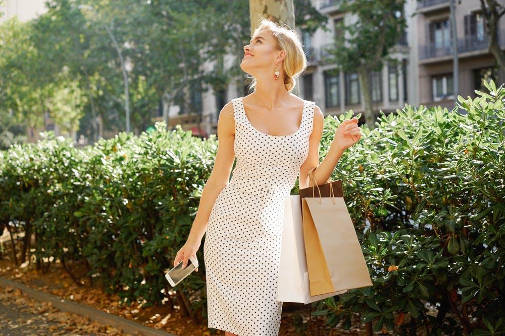 Woman posing outdoors wearing a white and black polka dot dress