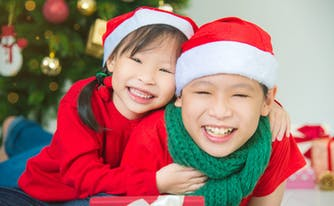 two children smiling in front of christmas tree