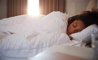 sleep stages - image of person sleeping in bed