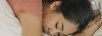 person sleeping on stomach in bed with arm under head