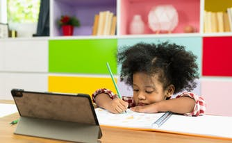 child at school writing in notebook