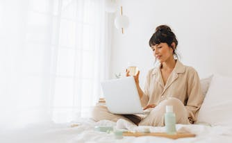 person working from home in bed drinking tea with laptop