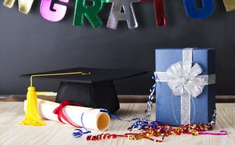 graduation cap and diploma next to graduation gift in a wrapped box