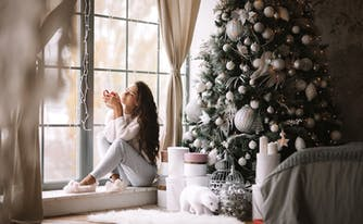 image of person in cozy loungewear sitting on windowsill in front of christmas tree