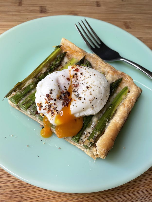 asparagus tart with poached egg over it
