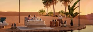 couple sitting on saatva mattress in middle of desert oasis in saatva commercial