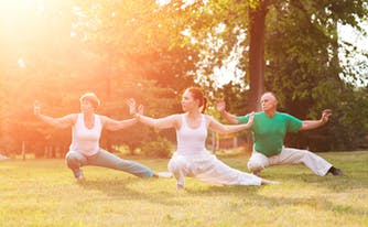 three people practicing tai chi outside