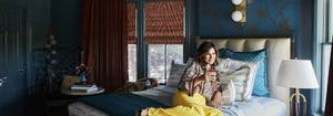 kaleidoscope project - rydhima brar, interio designer, sitting on bed at cornell inn