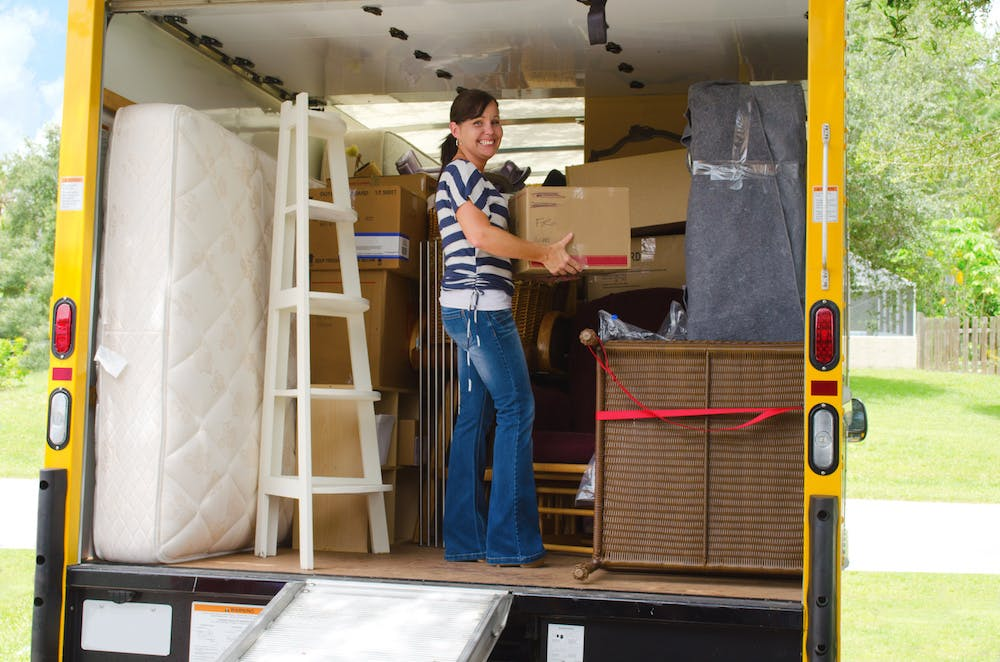 person holding box in moving truck with a mattress on its side in the truck