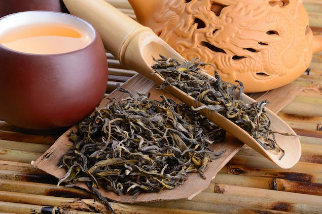oolong tea leaves on a spoon with cup of tea next to it