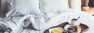 breakfast in bed featuring eggs, toast, and coffee on a tray