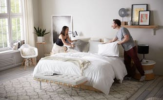couple making bed together