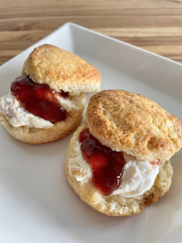 plate of two scones with clotted cream and jam