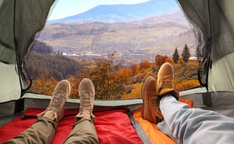 close-up of feet of two people lying down on sleeping bags inside tent
